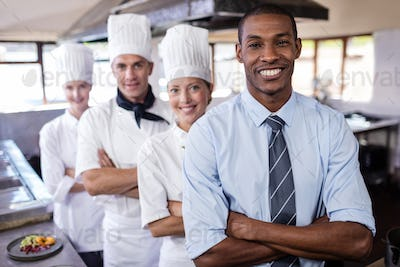Group of chefs and manager standing with arms crossed in kitchen