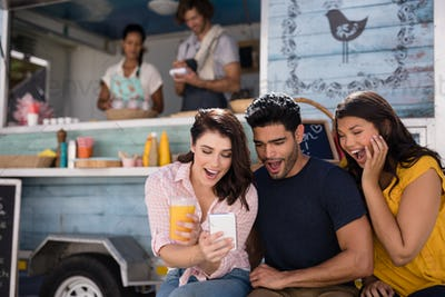Friends using mobile phone at food truck van