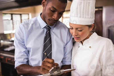 Male manager and female chef writing on clipboard in kitchen