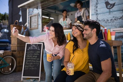 Friends taking selfie from mobile phone in food truck van