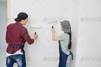 People applying matte white paint