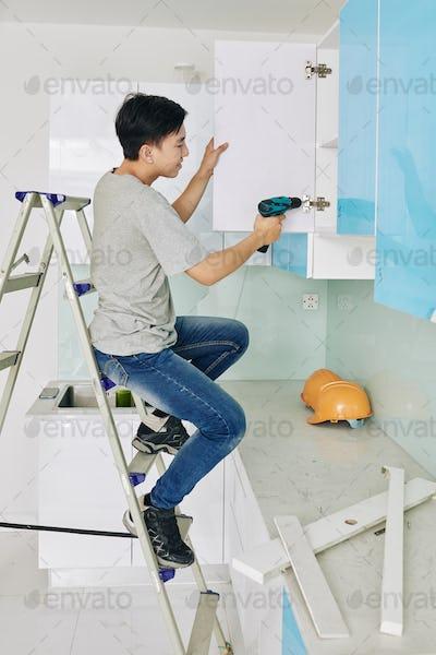 Man fixing cupboard door