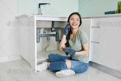Woman fixing pipe by herself