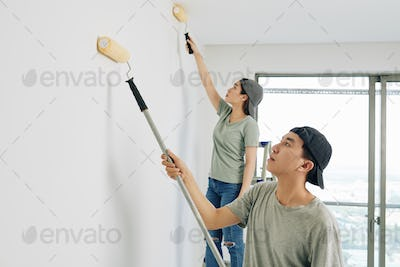 Young people painting walls