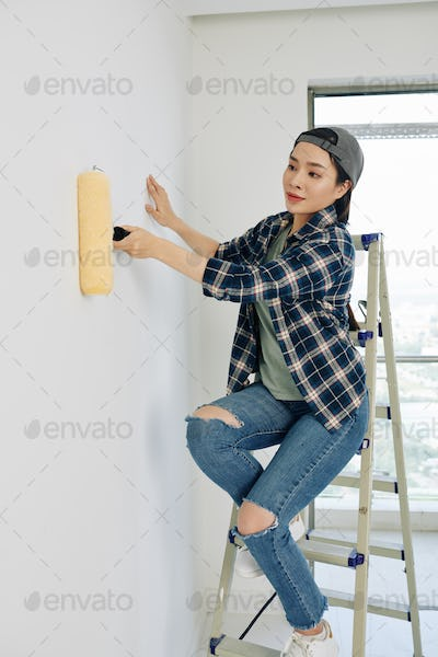 Woman painting house wall