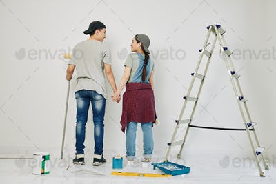 Couple starting painting wall