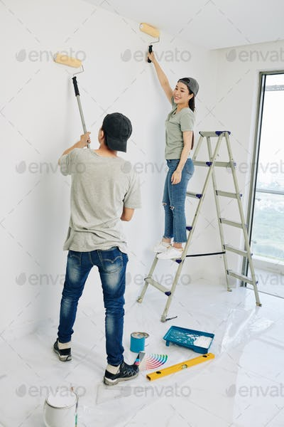Couple painting room walls