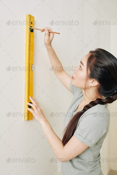 Woman drawing line on wall