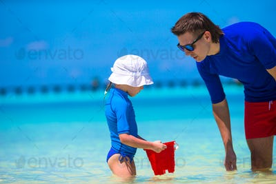 Happy father and little daughter have fun on tropical beach