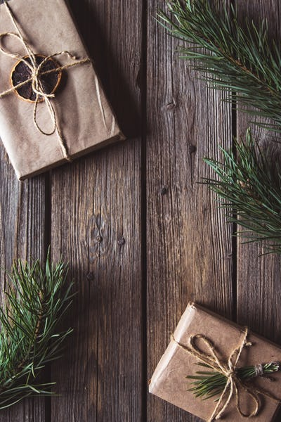 Christmas gifts for new year wrapped in craft paper near branches and cones on wooden background