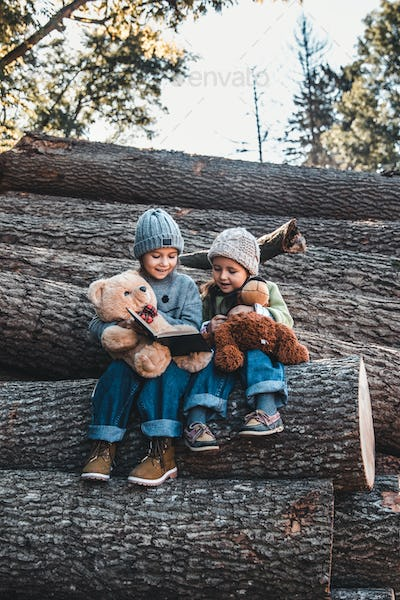 Two little girls reading books with a toy, sitting on a log. ?oncept of education and friendship