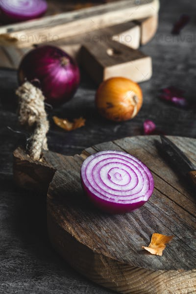 Red Onion Slices on wooden board with dark background
