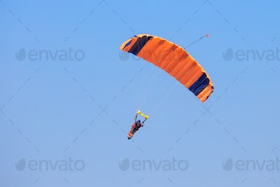 Skydiver under an orange parachute in blue sky
