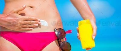 Closeup female hand applying with sunscreen on white beach