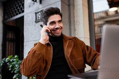 Young cheerful man happily talking on cellphone working on laptop in cafe on street