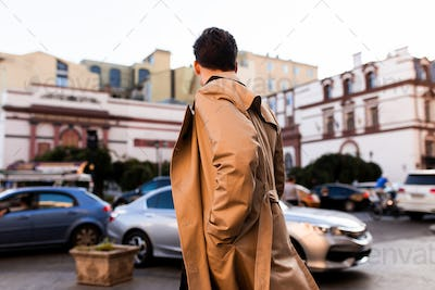 Back view of young stylish man in trench coat walking through street