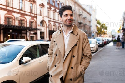 Young attractive smiling stylish man in trench coat happily walking through street