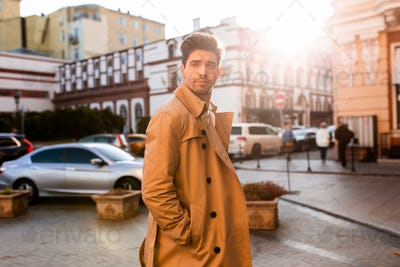 Young attractive stylish man in trench coat intently looking away on street
