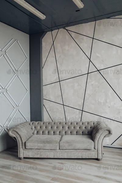 Modern sofa in grey stylish room. Empty modern sofa of grey color. Love seat modern couch in studio
