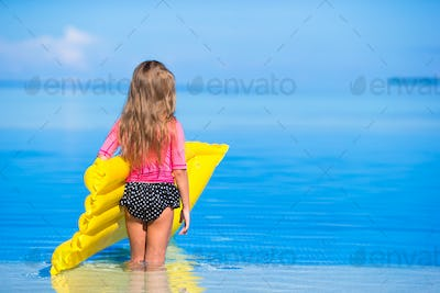 Adorable girl with inflatable air mattress in outdoor swimming pool