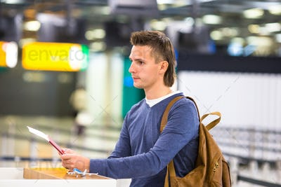 Beautiful man with passports and boarding passes at the front desk at airport