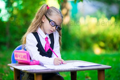 Adorable little school girl at desk with notes and pencils outdoor. Back to school