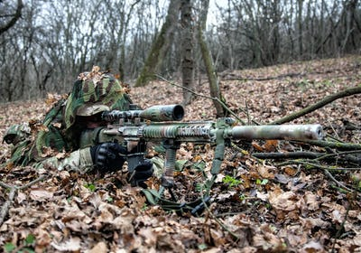 Army sniper hiding on ground in forest leaves