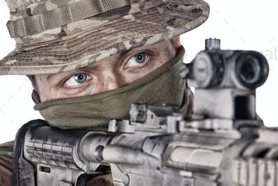 Close-up portrait of army soldier aiming rifle