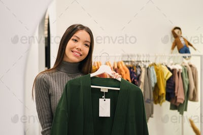 Beautiful stylish Asian girl happily trying on cardigan in fashion store