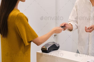 Close up young woman paying with credit card in store