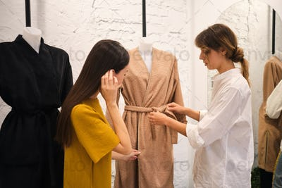 Young fashion designer showing coat from new collection to attractive girl in modern showroom