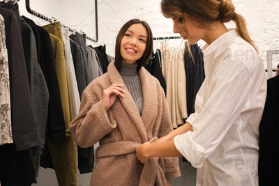 Young designer helping trying on coat from new collection to pretty Asian girl in clothes store