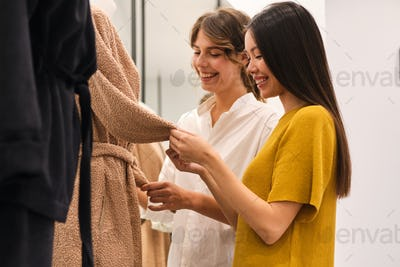 Two cheerful stylish girls happily choosing clothes in fashion store