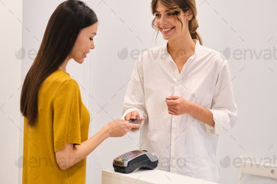 Young casual woman happily paying with credit card in fashion store