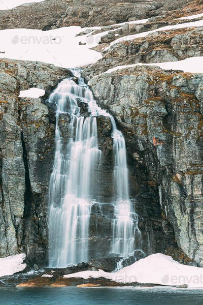 Road Aurlandsfjellet, Norway. Waterfall Flotvatnet In Spring Snowy Landscape. Scenic Route Road In