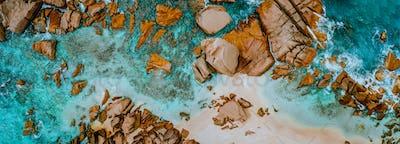Aerial top panorama view of ocean shore huge bizarre granite rocks boulders on tropical beach with