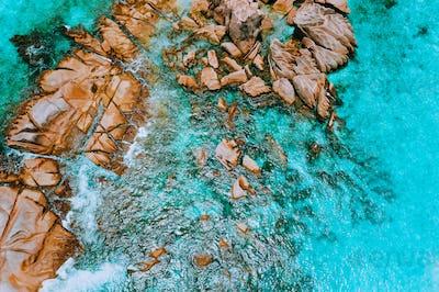 Aerial top view of ocean waves hitting granite rocks on the beach in La Digue, Seychelles