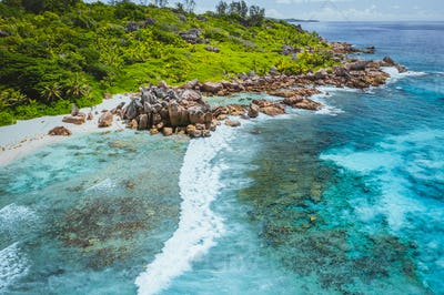 Tropical beach Anse Cocos. La Digue island. Seychelles. Drone aerial view of coastline with blue