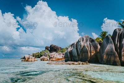 Famous granite boulders in lagoon with shallow ocean water and white cloudscape on amazing Anse