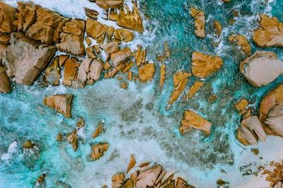 Aerial top view of tropical coastline. Bizarre granite rocks boulders, turquoise azure water