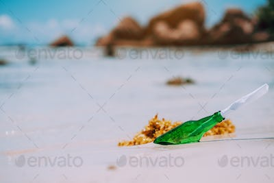 Bottle with message on white paradise sandy beach with blurred background. conceptual photo