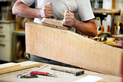 Carpenter working with a planer on a block of wood