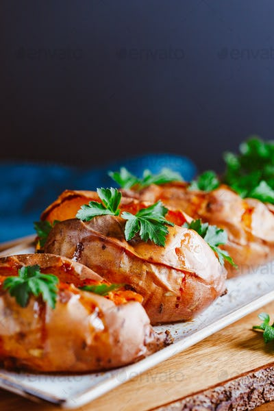 Baked three sweet potatoes with fresh parsley on a white ceramic dish