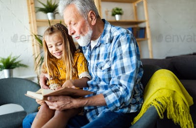 Bearded grandfather and his grandchild are having fun reading a book together