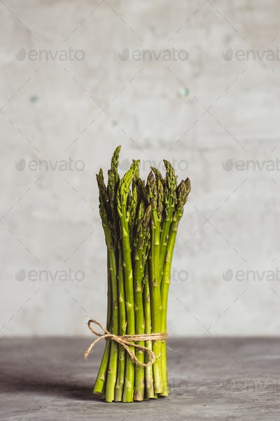 Fresh bunch of asparagus with smooth daylight on grey stone background/top view