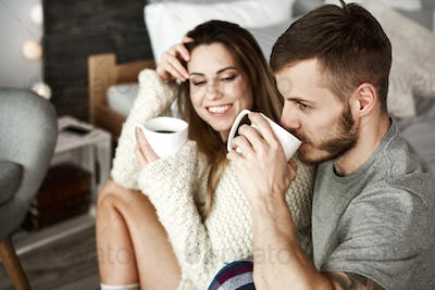 Cheerful man and woman drinking coffee in bedroom