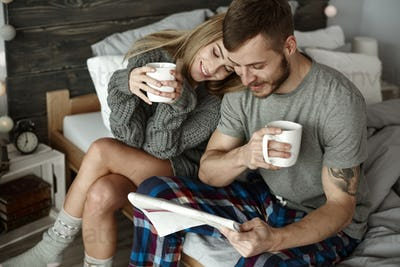 Affectionate couple with coffee reading newspaper