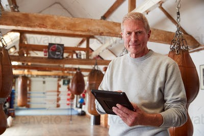 Portrait Of Senior Male Boxing Coach In Gym Tracking Training Using Digital Tablet