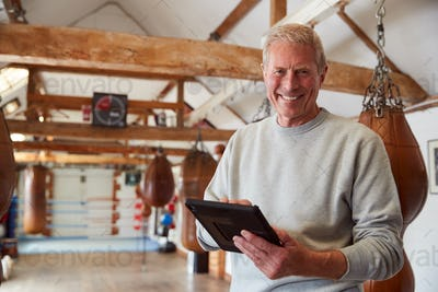 Portrait Of Smiling Senior Male Boxing Coach In Gym Tracking Training Using Digital Tablet