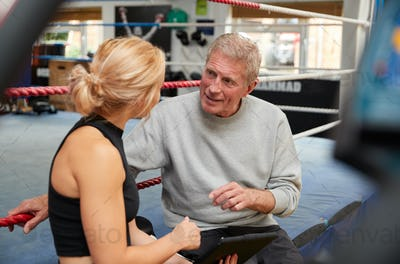 Female Personal Trainer With Senior Male Boxer In Gym Checking Performance Using Digital Tablet